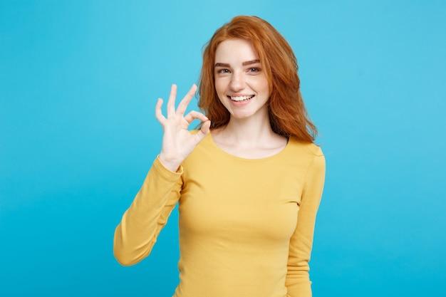주근깨가있는 매력적인 생강 빨간 머리 소녀의 재미와 사람들 개념 얼굴 만 초상화는 웃고 손가락 파스텔 블루 벽 복사 공간으로 확인 서명을 만들기