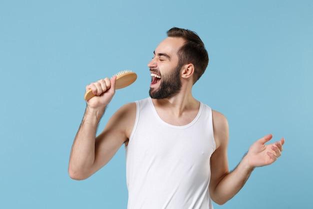 Забавный бородатый мужчина 20-х лет в белой рубашке поет, удерживая гребень, как микрофон, изолированный на голубой пастельной стене, портрет. концепция косметических процедур здравоохранения ухода за кожей.