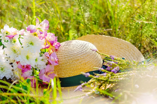 Fun beautiful yellow straw hat with green ribbon and bouquet of wild white pink violet flowers lie in green grass of big large wide summer hot spring sunny sunray light field between fruit trees