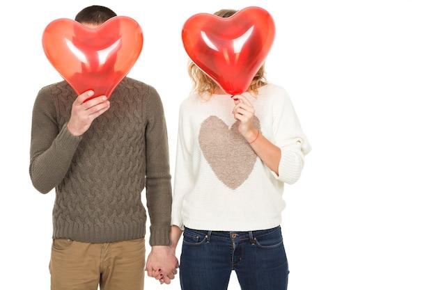 Весело быть вместе. студийный снимок влюбленной пары, держащейся за руки, пряча лица за красными воздушными шарами в форме сердца