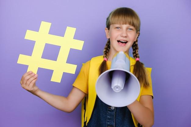 노란색 배낭을 메고 큰 해시태그 기호를 들고 메가폰으로 비명을 지르는 재미있는 금발 학교 십대 소녀, 보라색 배경 벽 어린이 스튜디오 위에 고립된 포즈. 교육 라이프 스타일 개념