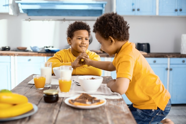 Fun at breakfast. curly-haired little boy sitting at the table next to his elder brother and teasing him, trying to poke his chin while they having breakfast