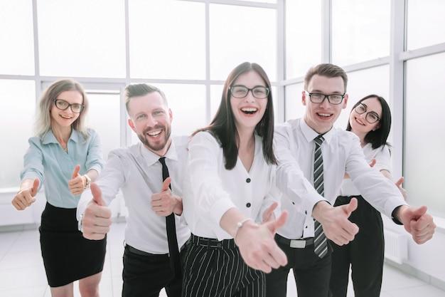 Весело бизнес-команда показывает палец вверх. концепция успеха
