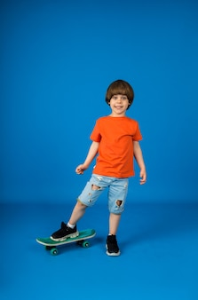 Fun caucasian toddler is playing with a skateboard on a blue surface with space for text. vertical orientation