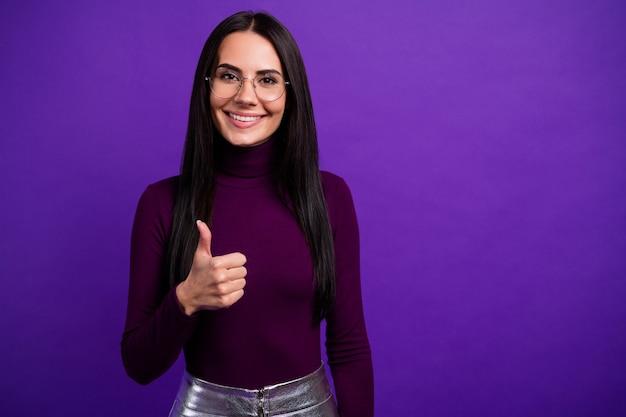 Весело веселая позитивная милая женщина работает консультантом изолированно показывает палец вверх яркий цвет фиолетовая стена