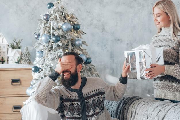 재미있는 크리스마스 축하. 레이디는 남자 친구에게 깜짝 선물을 준비했습니다. 현재 궁금한 사람, 눈을 가리고 웃고 있습니다.