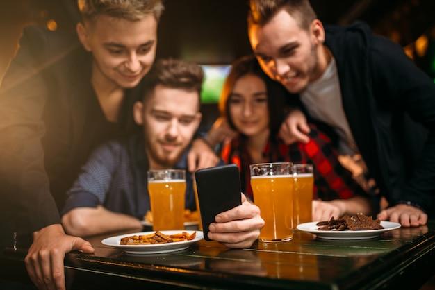Веселая компания смотрит фото на телефоне в спорт-баре