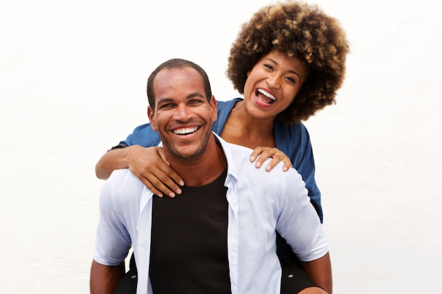 Fun couple laughing in embrace by white wall