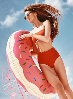楽しさは、赤いビキニを着て、膨らませて浮き輪を持っている熱意とエネルギーのセクシーな女性を作成します
