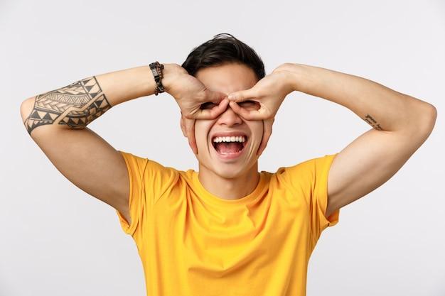Концепция веселья, азарта и энтузиазма. веселый и беззаботный игривый азиатский татуированный парень в желтой футболке, делающий очки или маску супергероя с пальцами на глазах, радостная белая стена