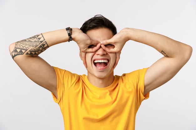 Fun, excitement and enthusiasm concept. cheerful and carefree playful asian tattooed guy in yellow t-shirt, making glasses or superhero mask with fingers over eyes, standing white wall joyful