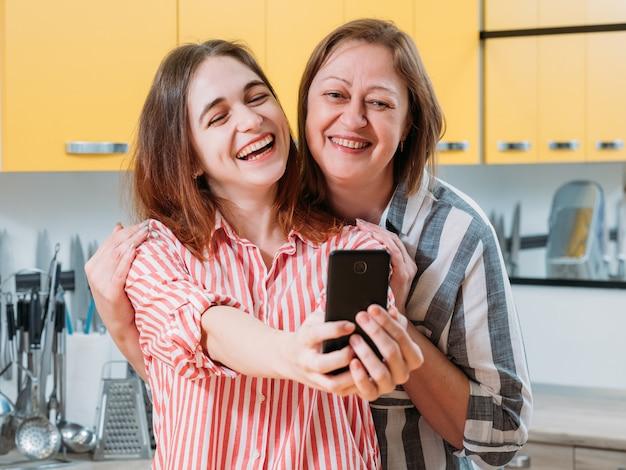 즐거운 가족 여가. 행복 한 엄마와 딸이 함께 시간을 즐기고, 스마트 폰을 사용 하여 부엌에서 셀카를 복용 웃 고.