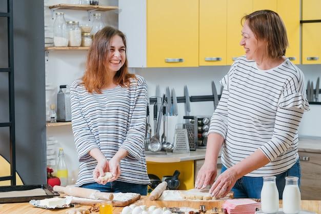 부엌에서 재미있는 가족 레저. 엄마와 딸 함께 요리를 즐기고, 반죽 요리, 웃고.