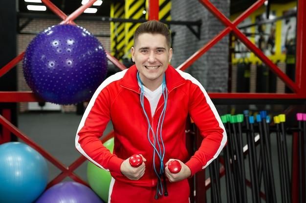 Весело фитнес спортивный парень с гантелями и скакалкой в тренажерном зале. обучение, концепция образа жизни спортивной мотивации.