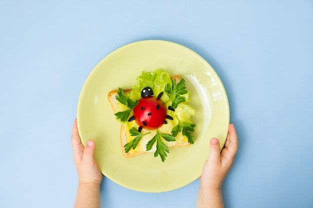 Fun food art for kids. children's hands hold plate with ladybug sandwich on blue wall. how to make creative breakfast for kid at home. step by step instruction, view from above