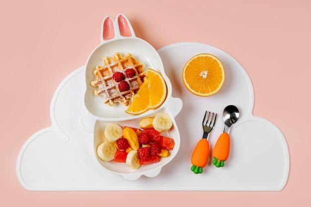子供のための楽しい食べ物。子供の朝食。ワッフルとフルーツのバニーの形をしたかわいいプレート。子供のための食品のアイデア。