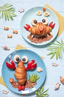 子供のための楽しい食べ物。子供の朝食のためのフルーツとかわいいカニとロブスターのクロワッサン