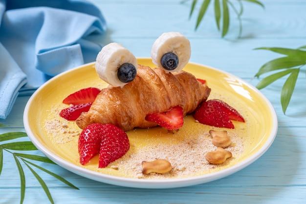 子供のための楽しい食べ物。子供の朝食のためのフルーツとかわいいカニクロワッサン