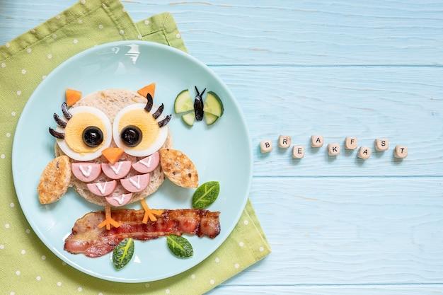 子供のための楽しい食べ物-ソーセージと卵が入ったかわいいコキンメフクロウのサンドイッチトースト
