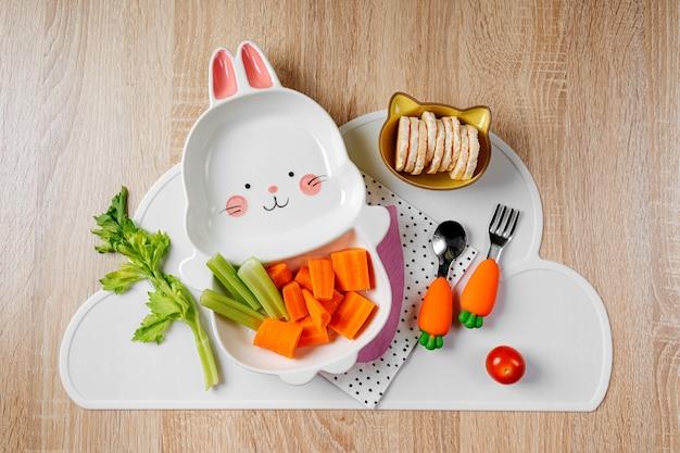 子供のための楽しい食べ物。新鮮な野菜とうさぎの形をしたかわいいプレート。子供のための食品のアイデア。にんじんを使った子供の健康食品