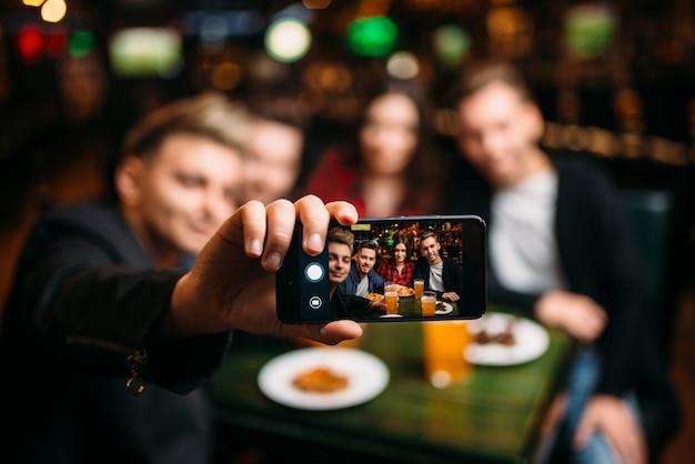 楽しい友達がスポーツバーの電話カメラで自分撮りをし、サッカーファンの幸せな余暇を作る