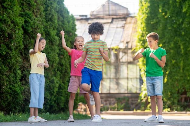 Забавная игра. кудрявый мальчик стоит в центре с веселыми азартными друзьями, активно играющими вместе в парке в погожий день
