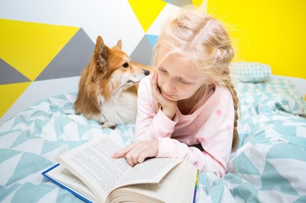 保育園のベッドで楽しい女の子と犬のコーギーが本を読んだ。ホームスクーリング