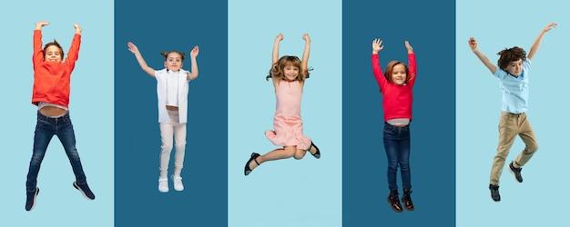 재미있는. 파란색 스튜디오 배경에서 화려한 캐주얼 옷을 입고 점프하는 초등학교 어린이 또는 학생들의 그룹. 창의적인 콜라주. 학교, 교육, 어린 시절 개념으로 돌아가십시오. 쾌활한 소녀와 소년.