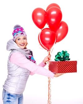 Весело счастливая взрослая женщина дает красную подарочную коробку, изолированную на белом