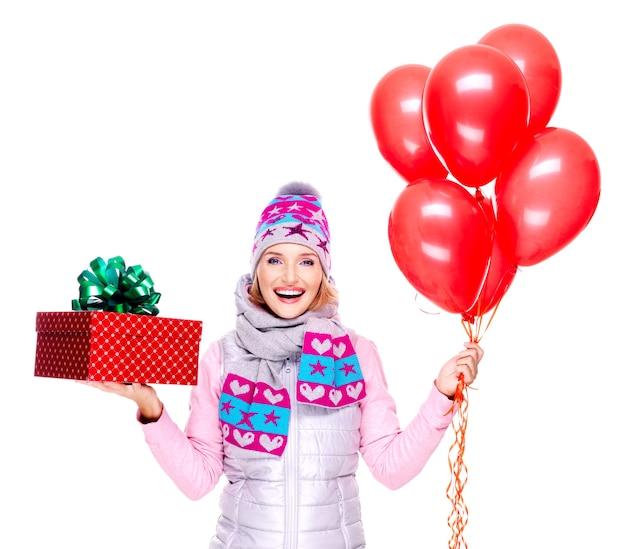 Divertente donna adulta felice con confezione regalo rossa e palloncini isolati su bianco
