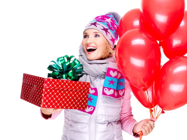 Fun happy adult woman with red gift box and balloons isolated on white