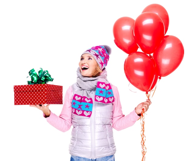 Fun happy adult woman with red gift box and balloons looking up isolated on white