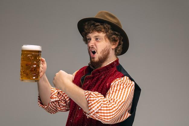 楽しい。灰色のスタジオの背景にビールのジョッキで身振りで示す伝統的なオーストリアまたはバイエルンの衣装を着た幸せな男。コピースペース。お祝い、オクトーバーフェスト、お祭り、伝統のコンセプト。