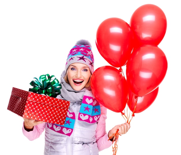 Fun happy young woman with red gift box and balloons isolated on white