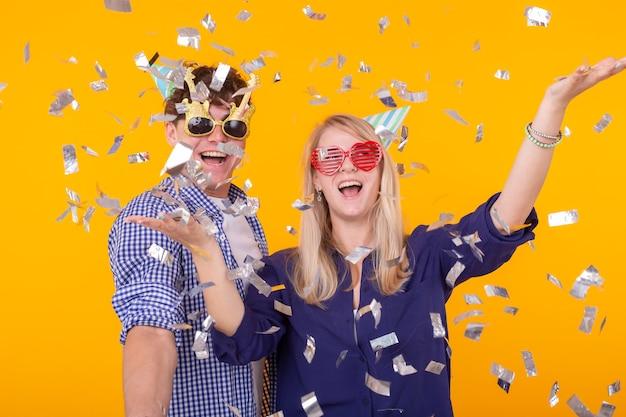 Концепция веселья, праздников и вечеринок - пара танцует среди падающих конфетти на желтой стене
