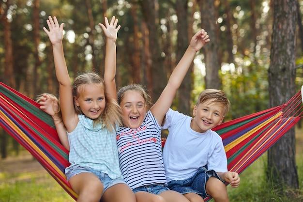 정원에서 재미. 다채로운 해먹에서 노는 사랑스러운 아이들