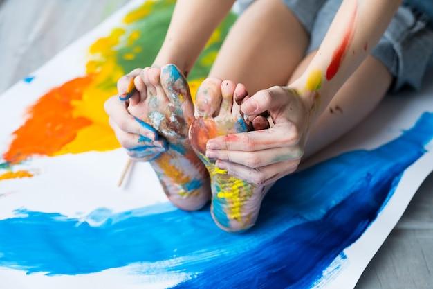 楽しいレジャー。カラフルな絵の具で汚れた抽象的なアートワーク、足と手の上に床に座っているアーティストのトリミングされたショット。