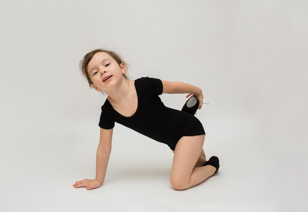 楽しい小さな体操の女の子が白い背景でウォームアップを行います