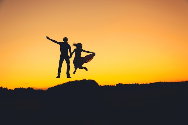 Fun loving couple jumping at sunset, silhouette