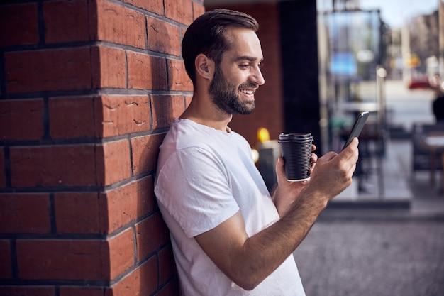 스마트 폰을 찾고 커피와 함께 재미있는 남자