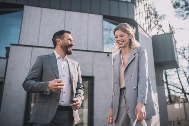 楽しい気分。ビジネス大人のひげを生やした男性が話し、若いブロンドの女性がオフィスの近くで屋外に立って通信を笑っている