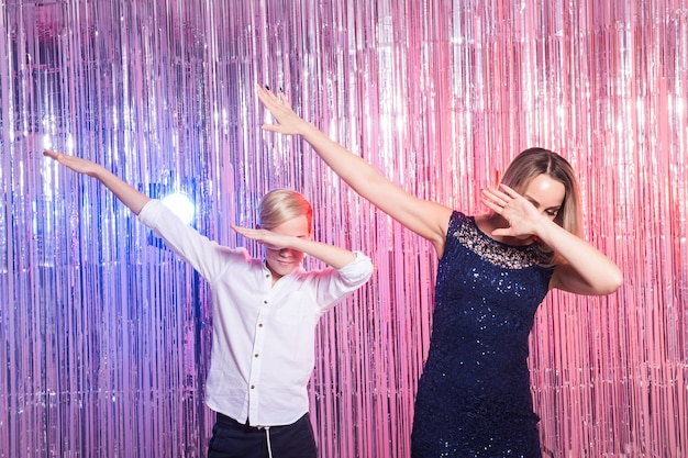 Fun, mothers day, children and family concept - teen boy and his mom funny dancing shiny party
