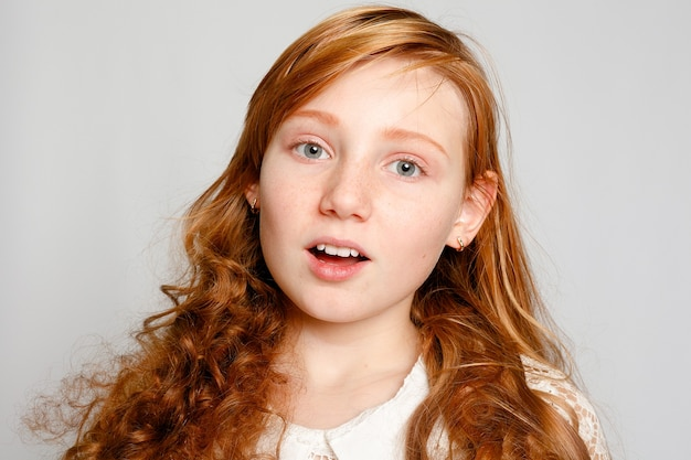 Fun portrait of an adorable red haired girl on a grey background. beauty, kid fashion, cosmetics, healthy hair. hairdresser, makeup, shampoo.
