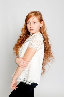 Fun portrait of an adorable red haired girl on a grey background beauty kid fashion