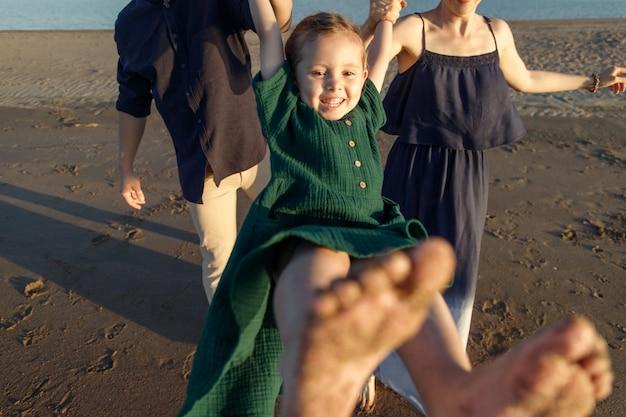 야외에서 부모님의 팔에 흔들리는 녹색 드레스를 입은 행복한 소녀의 재미있는 초상화.