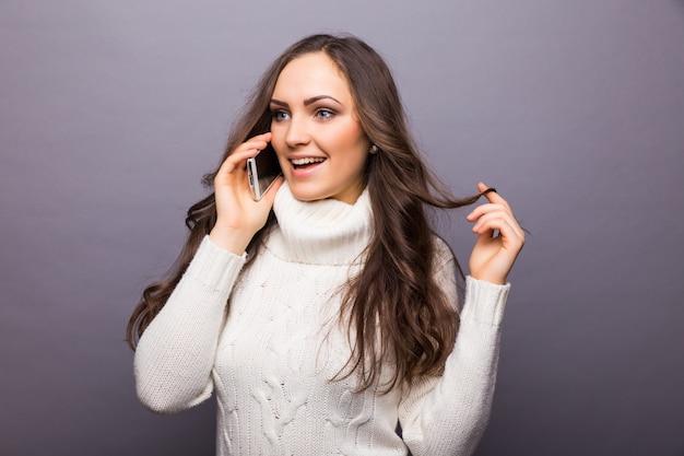 笑っている魅力的な若い女性が携帯電話でおしゃべりする眼鏡をかけている、灰色の壁の上半身
