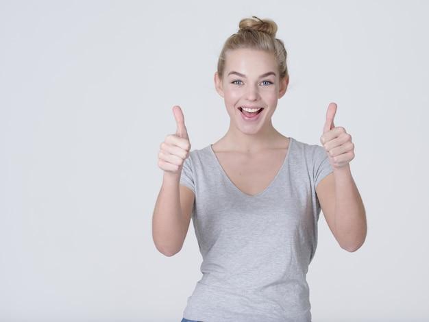親指をあきらめる女性の楽しい肖像画-白い背景で隔離