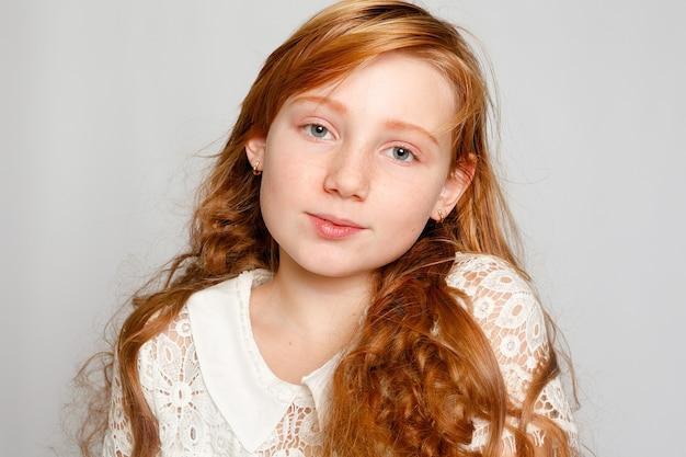 Забавный портрет очаровательной рыжеволосой девушки на сером фоне. красота, детская мода, косметика, здоровые волосы. парикмахерская, макияж, шампунь.