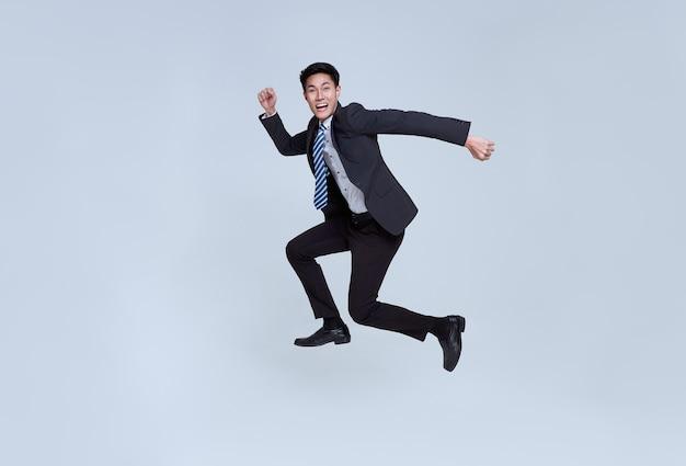 スタジオの背景に空中でジャンプする幸せでエネルギッシュな若いアジアのビジネスマンの楽しい肖像画
