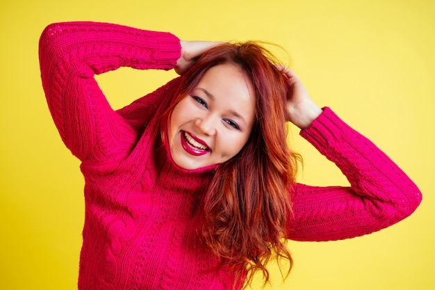 Fun redhead woman putting on (removes) sweater in studio on a yellow background